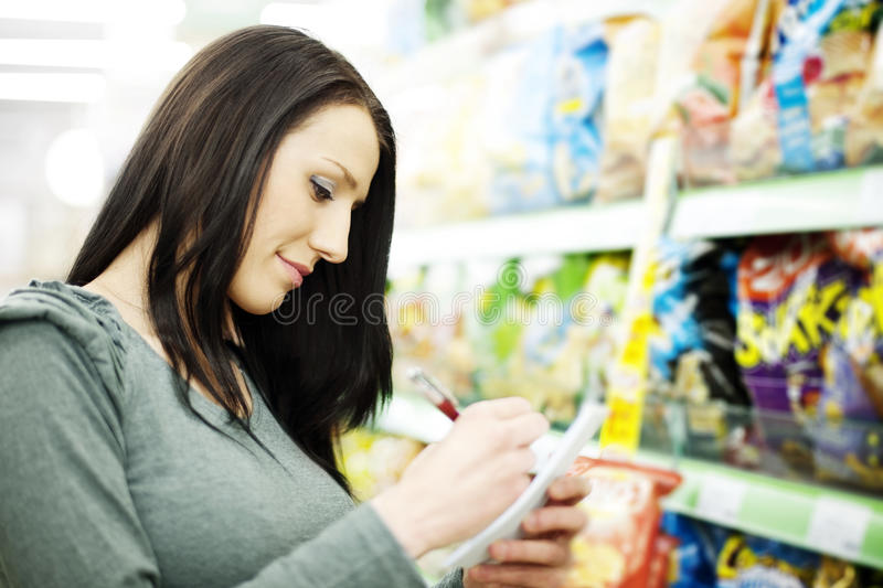 Shopping list. Supermarket collection: woman checking her shopping list royalty free stock photos