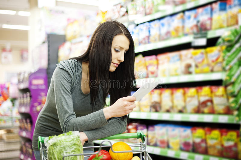 Shopping list. Supermarket collection: woman checking her shopping list stock image