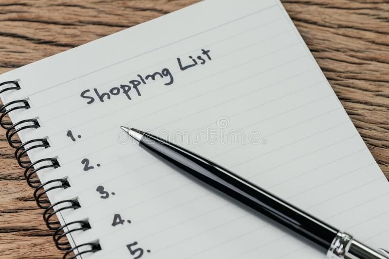 Shopping List, checklist to buy things from supermarket concept, pen with small notepad paper with handwriting headline as royalty free stock image