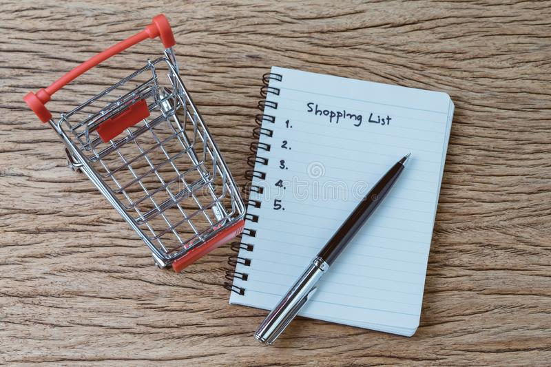 Shopping List, checklist to buy things from supermarket concept, pen with small notepad paper with handwriting headline as stock photos