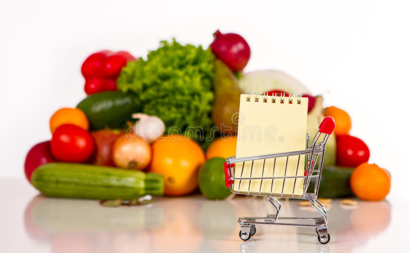 Shopping list in a food shop. Fruits and vegetables in the background. in the foreground grocery trolley with a notebook and pen stock photography