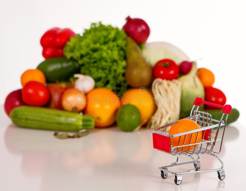 Shopping list in a food shop. Fruits and vegetables in the background. in the foreground grocery trolley with a notebook and pen royalty free stock photography