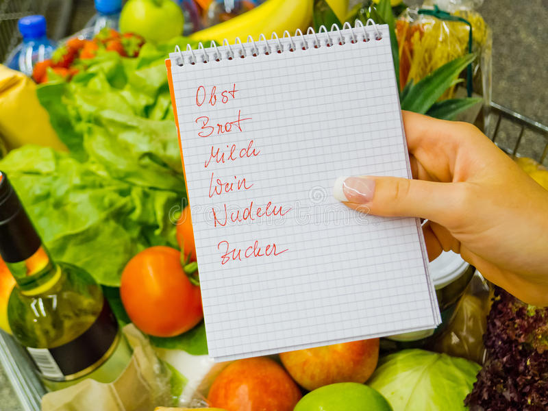 Shopping list at the supermarket (german). A woman holding a shopping list in a supermarket in the hand. german language stock photography