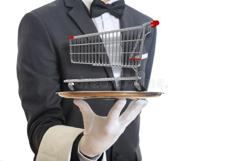 Waiter holding a silver platter with an empty shopping trolley, on white background. 3d illustration. Shopping luxury service concept. Waiter holding a silver royalty free stock photography