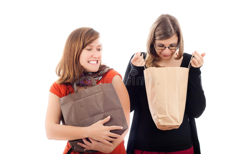 Shopping madness. Concept, two young excited women shopping, isolated on white background stock photos