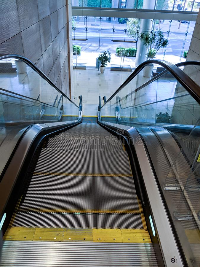 Shopping Mall Escalator. Escalator moving staircase between street entrance to a shopping mall and next floor level royalty free stock images