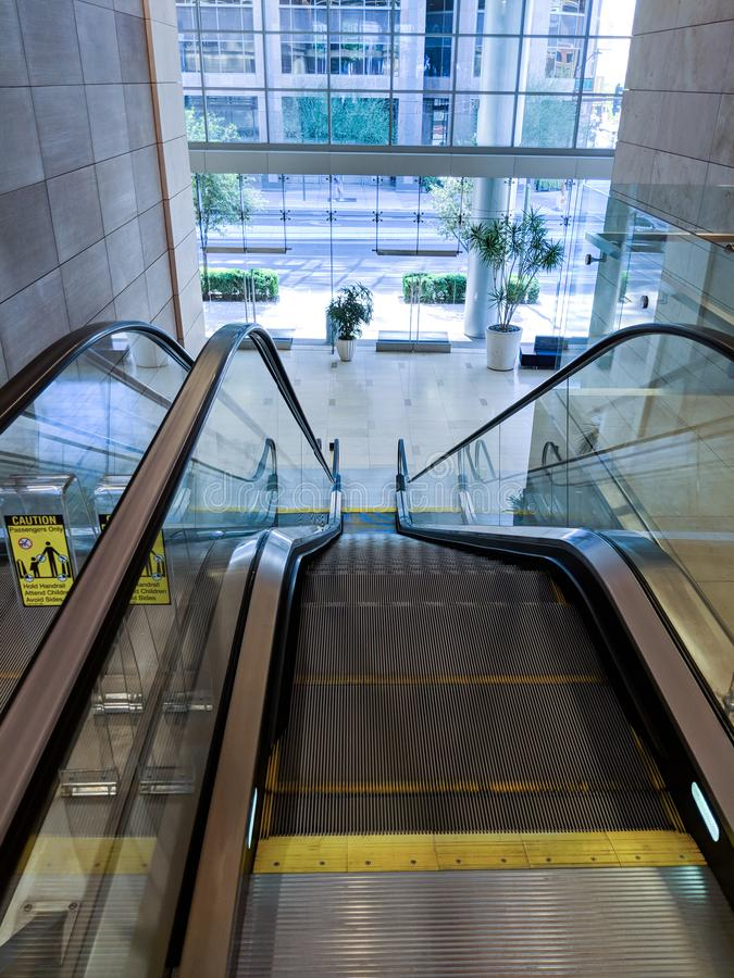 Shopping Mall Escalator. Escalator moving staircase between street entrance to a shopping mall and next floor level royalty free stock photo