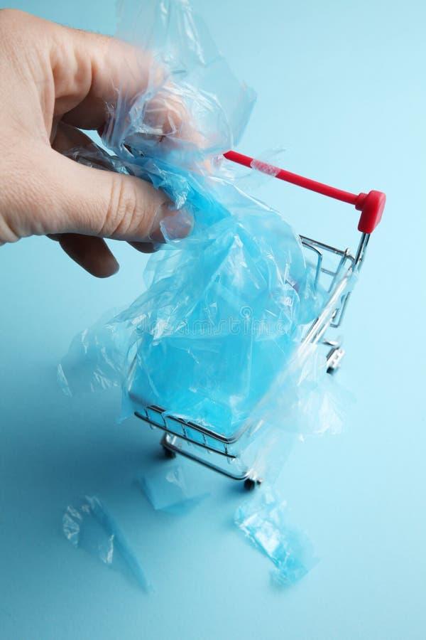 Shopping med plastpåsar förorenar planeten arkivbild