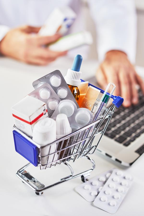 Shopping for medicines online. With a shopping cart filled with a variety of tablets, bandages, bottles and thermometer in the foreground with a doctor or royalty free stock image