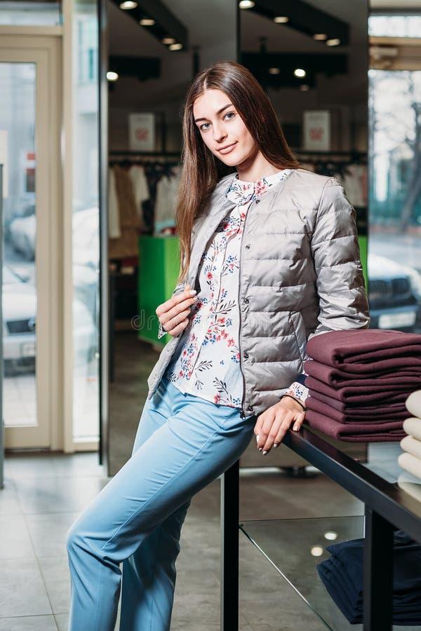 Shopping, mode, stil, försäljning, shopping, affär och folk härlig lycklig ung kvinna för begrepp i klädlager Affär arkivbild