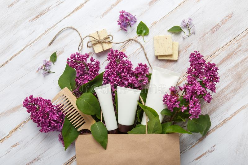 Shopping of natural woman cosmetics with spring lilac bloom. stock photography