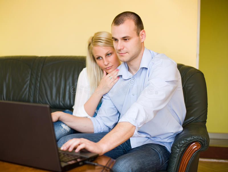 Shopping online. Portrait of attractive young couple shopping online using laptop at home royalty free stock photos