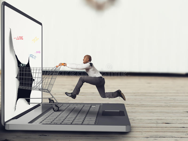 Shopping online. Businessman pushes a Shopping cart on the keyboard of laptop royalty free stock photography