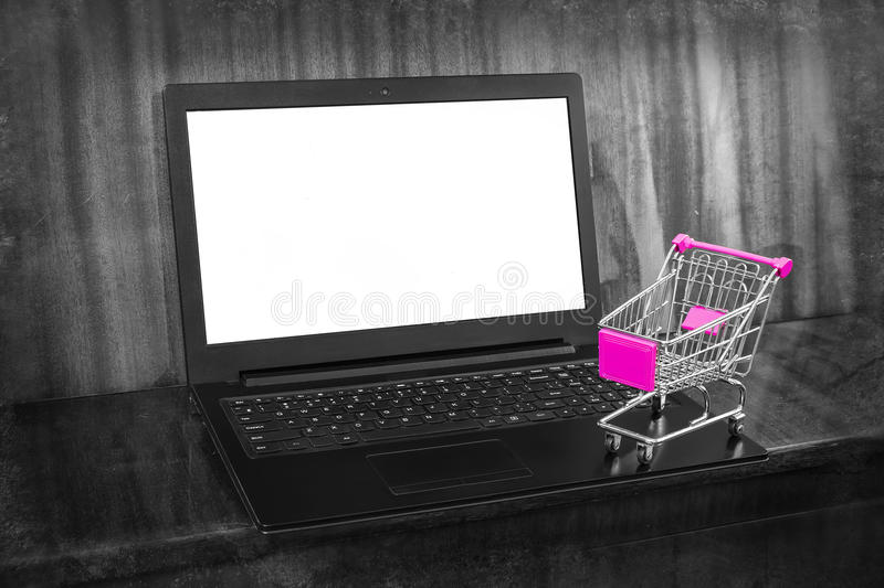 Shopping Online. Shopping cart and laptop with white screen for your text stock image