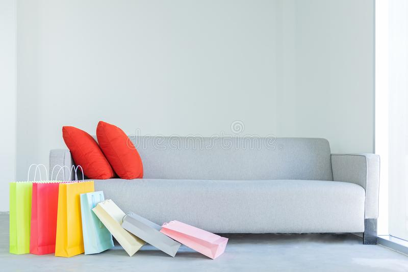 Shopping online. Colorful shopping bags with red pillow. On sofa in the living room stock image