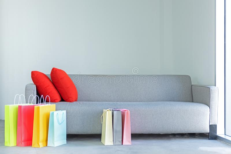 Shopping online. Colorful shopping bags with red pillow on sofa. In the living room stock images