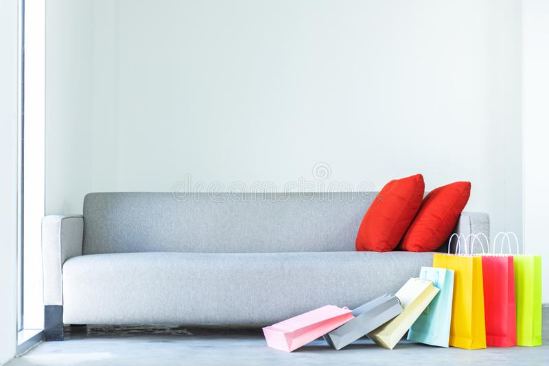 Shopping online. Colorful shopping bags with red. Pillow on sofa in the living room royalty free stock photography