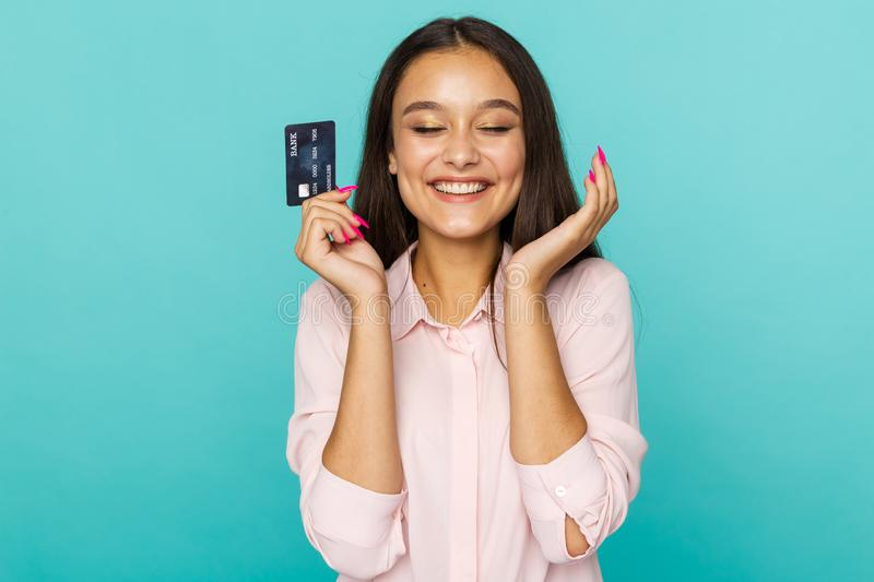 Shopping online concept. Attractive woman smiling and holding credit card isolated over the blue background. Shopping online concept. Attractive woman smiling stock image