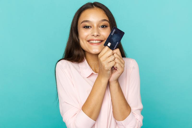 Shopping online concept. Attractive woman smiling and holding credit card  over the blue background. Shopping online concept. Attractive woman smiling and stock images