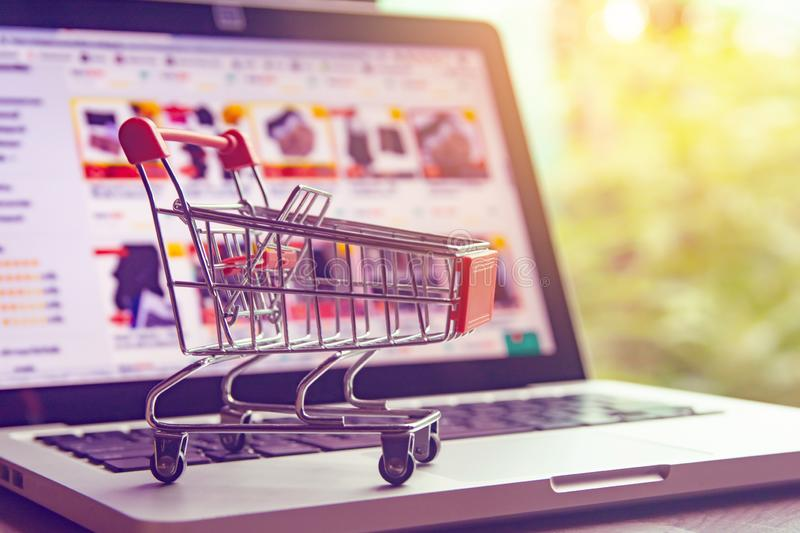 Shopping online concept - shopping cart or trolley on a laptop keyboard. Shopping service on The online web.  stock image