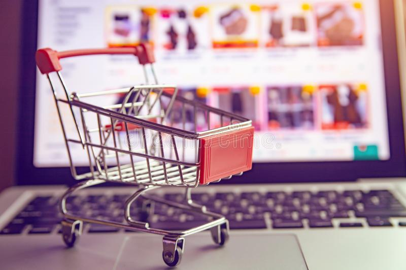 Shopping online concept - shopping cart or trolley on a laptop keyboard. Shopping service on The online web.  royalty free stock image