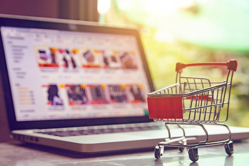 Shopping online concept - shopping cart or trolley on a laptop keyboard. Shopping service on The online web.  stock photo
