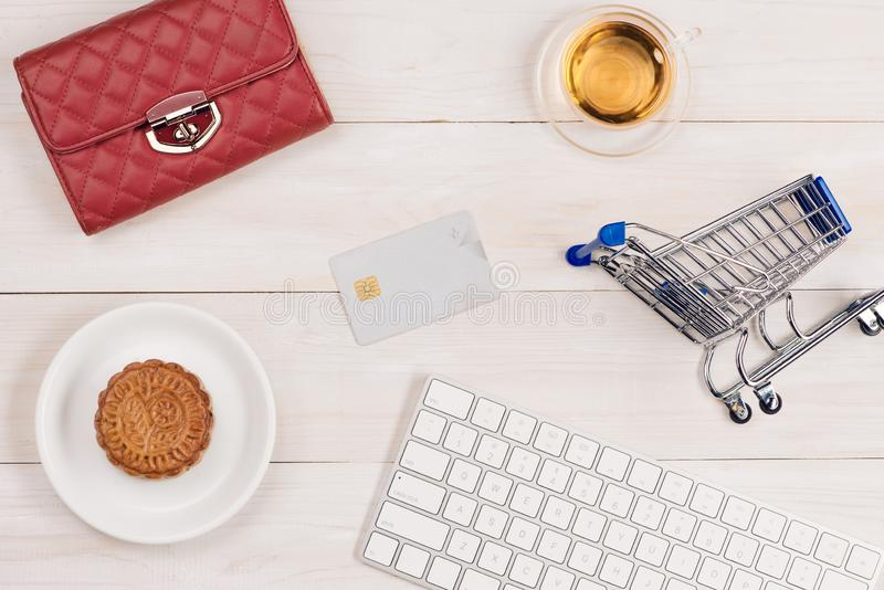 Shopping online concept. small red trolley and gadgets on light background.  royalty free stock photo