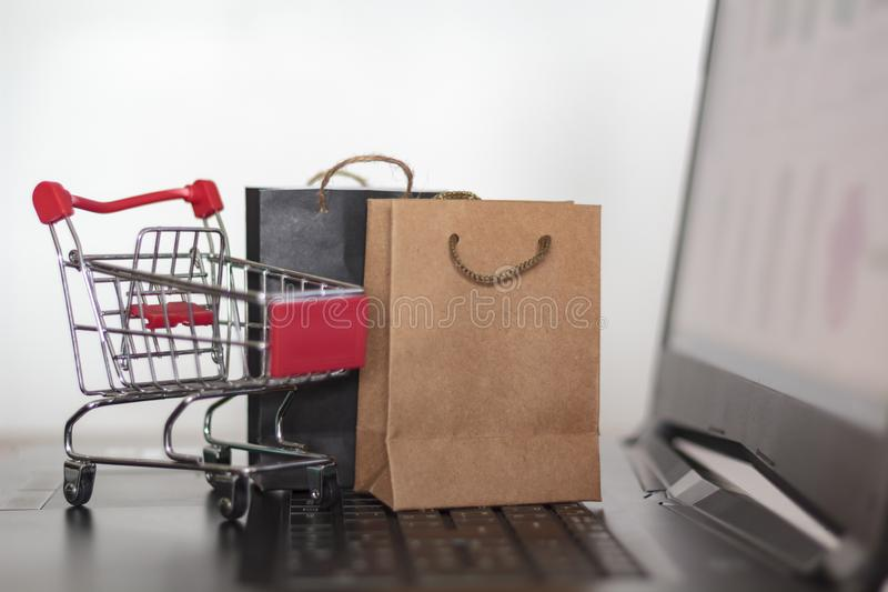 Shopping online and e-commerce concept. Trolley and shopping bags on laptop royalty free stock images