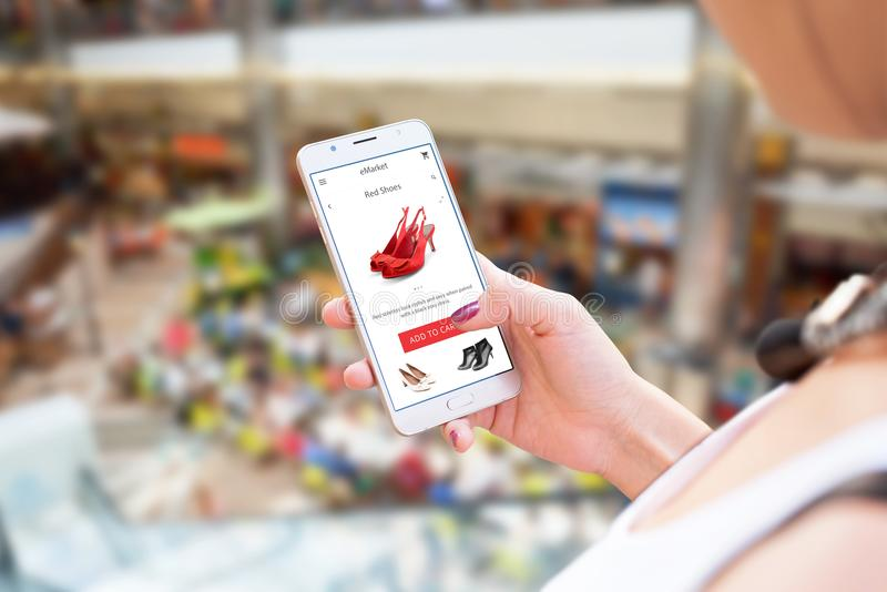 Shopping online with mobile phone. Woman holding smart phone. Shoes on app or web site. Shopping mall in background royalty free stock image