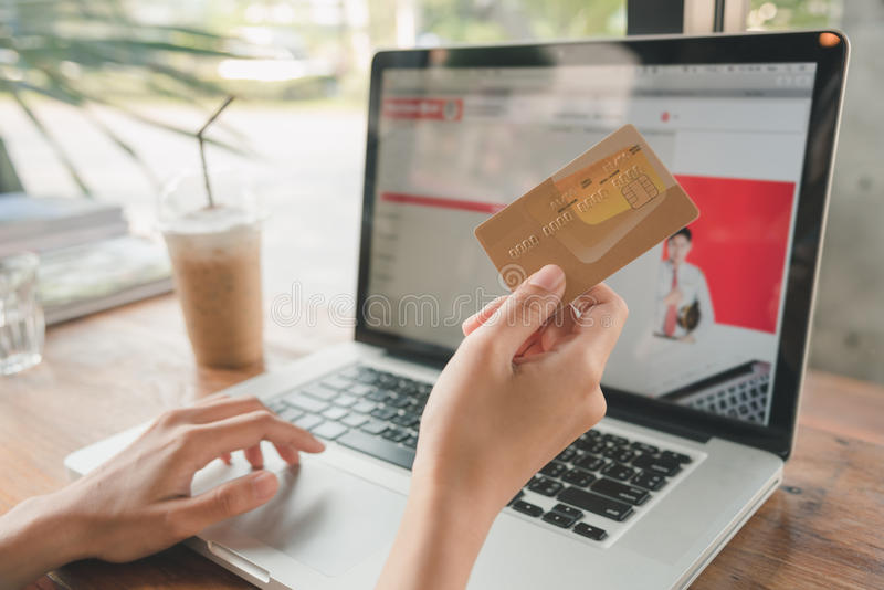 Shopping online (payment concept). Hand holding credit card shopping online (payment concept stock photos