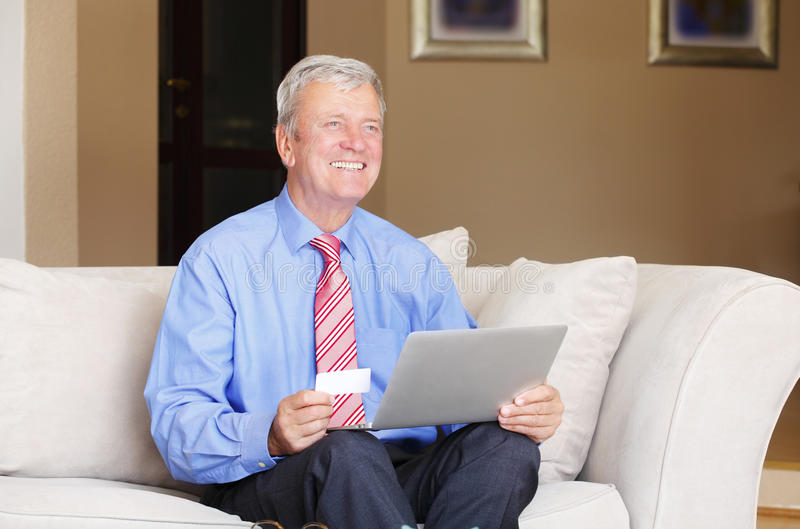 Shopping online. Portrait of retired senior man sitting at sofa while holding credit card in his hands and shopping online with laptop stock photo