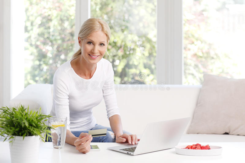 Shopping online. Portrait of smiling woman sitting at sofa in front of laptop and holding credit card in her hand while shopping online stock images