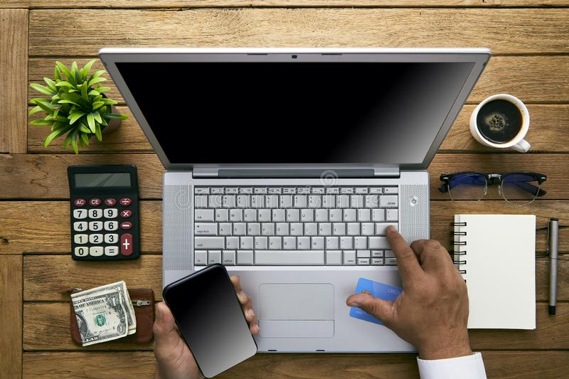 Shopping online smart phone and bank card. Shopping online at home using a laptop and a credit card, he is making a mobile payment using his smartphone, top view stock photography