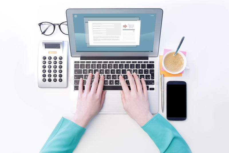 Shopping online. View from above of businesswoman sitting at desk and typing on laptop's keyboard while shopping online. Isolated on white background royalty free stock photo