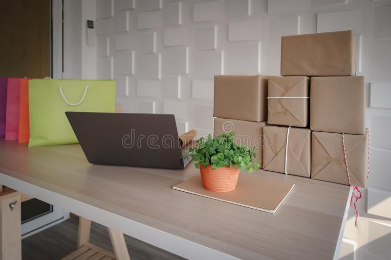 Shopping paper bags with laptop and plastic small tree in the orange pot royalty free stock photos