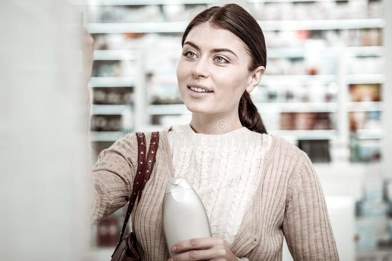 Good-looking woman smiling while shopping in pharmacy store on weekend stock image