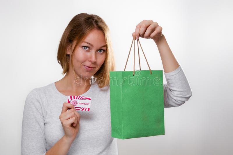 Shopping. Portrait of a blonde woman holding a Bank card and a green cardboard shopping bag. White background stock photo