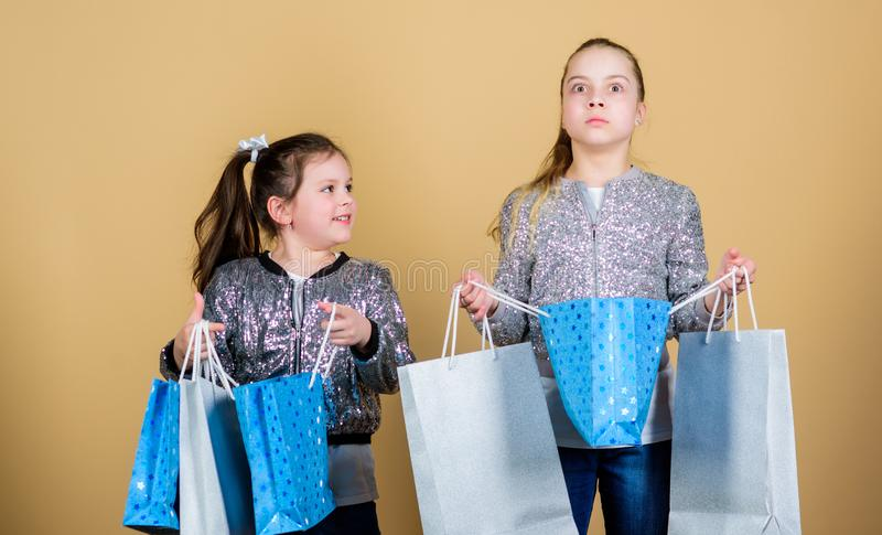 Shopping and purchase. Black friday. Sale and discount. Shopping day. Children hold bunch packages. Kids fashion. Expect. More. Pay less. Girls sisters friends royalty free stock photo