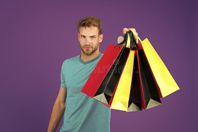 Shopping or sale and cyber monday. Man with shopping bags on violet background. Macho with colorful paper bags. Fashion royalty free stock photo