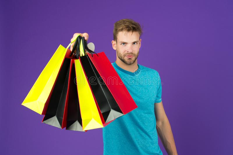 Shopping or sale and cyber monday. Man with shopping bags on violet background. Macho with colorful paper bags. Fashion shopper in royalty free stock photo
