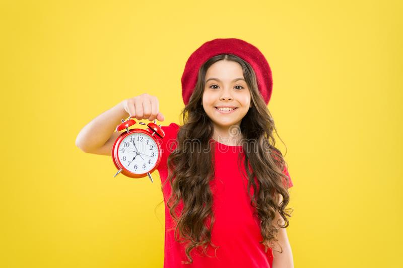 Shopping, sales and time concept. parisian child on yellow. child with alarm clock. Timeless fashion. happy girl with stock photo