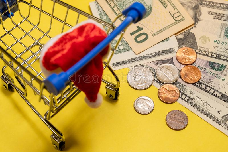 A shopping souvenir stroller with a Santa Claus hat costs about US dollars and cents. Americans spend on Christmas and New Year. A shopping souvenir stroller for royalty free stock photos