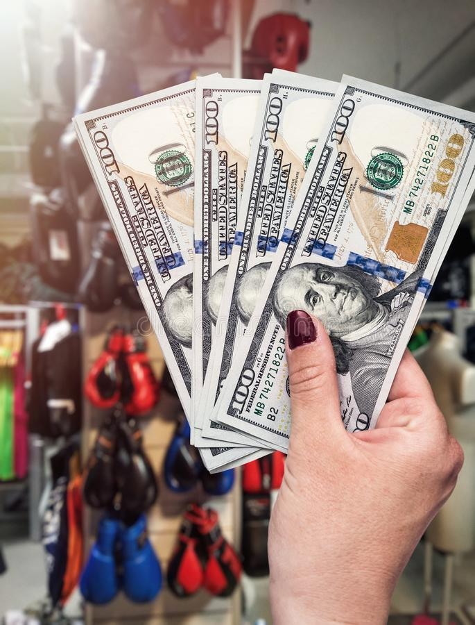 Shopping in sport equipment store, hand with dollars. stock photos