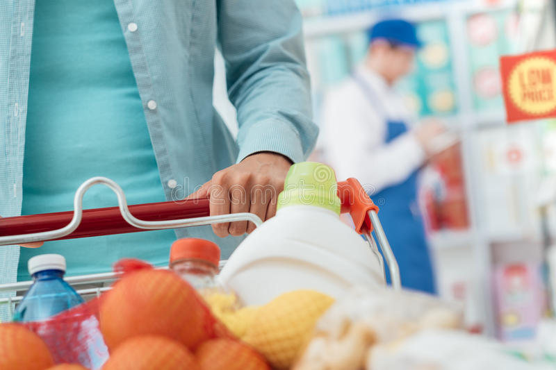 Shopping at the store. Woman shopping at the supermarket and pushing a full cart, clerk working on the background, hand detail close up stock image