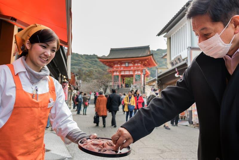 Shopping street in Kiyomizu-dera Temple. Kyoto, Japan- March 2, 2015 : Unidentify tourists tasted traditional japan sweet in souvenir shop on walkway to Kiyomizu stock photo