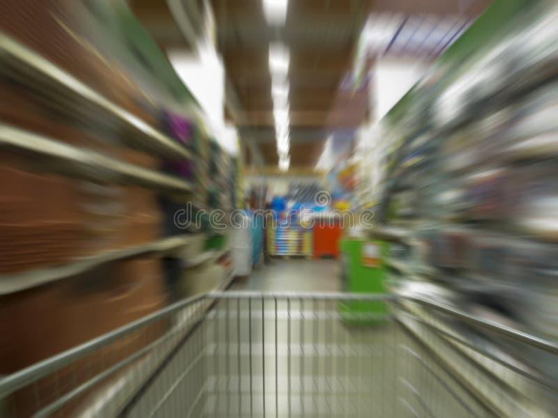 Shopping stress. Shopping cart speeding down the supermarket aisle royalty free stock photo
