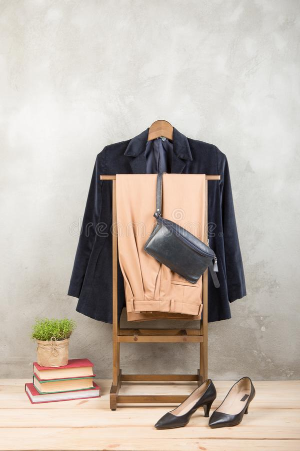 Shopping and style concept - clothes rack with trendy blue jacket and pants, bag and shoes on wooden floor and grey concrete. Background. Vertical photo royalty free stock image
