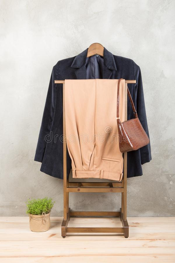 Shopping and style concept - clothes rack with trendy blue jacket and pants, bag on wooden floor and grey concrete background. Vertical photo, clothing stock photos