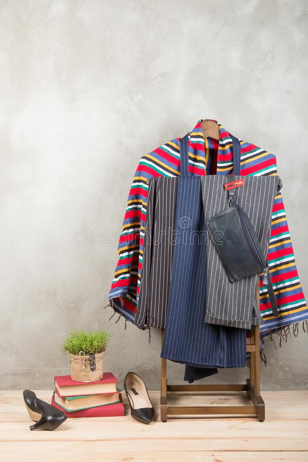 Shopping and style concept - clothes rack with trendy striped pants and plaid, shoes, bag on wooden floor and grey concrete royalty free stock image