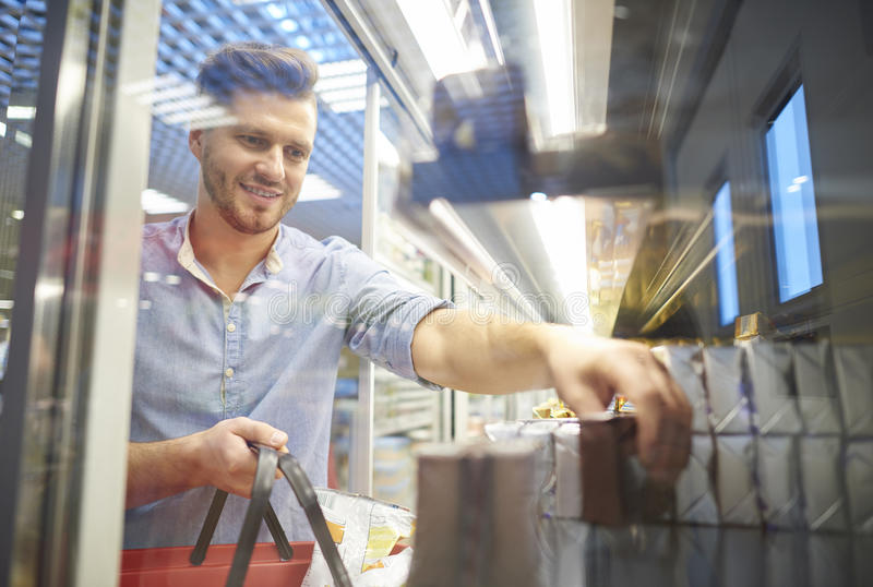 Shopping at the supermarket. Man shopping for groceries in supermarket freezer stock photography